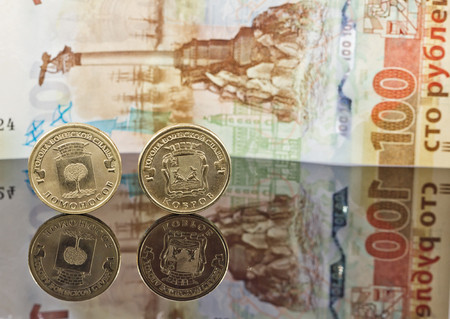 annexation: Commemorative coins 10 rubles cities of military glory Lomonosov and Carpets on the background of the banknote in a hundred rubles on the accession of Crimea to Russia