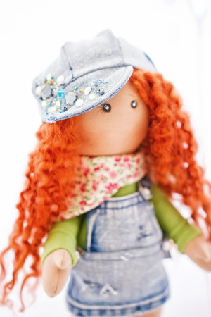 impish: The red-haired handmade doll dressed in a denim clothing in a cap adorned with rhinestones