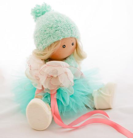 Muñeca de la materia textil con pelo rubio natural, sombrero de tejido de punto y de color verde claro vestido Foto de archivo - 58658709
