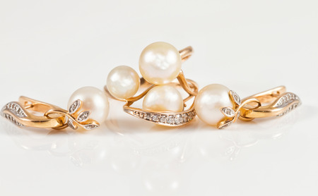 fine gold: set of fine gold jewelry with pearls on a white reflective surface
