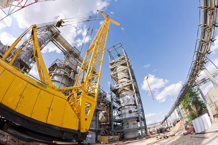 Yellow heavy-duty crawler crane works with refinery