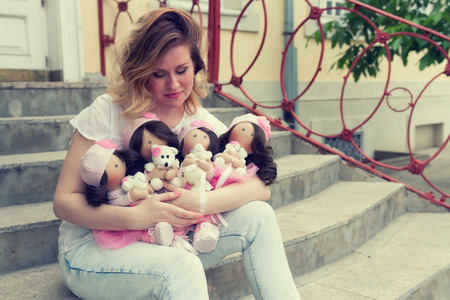 collectible: Creator of collectible dolls with natural hair sits with them in an embrace on the concrete steps