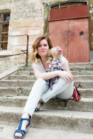 collectible: Blonde sits on the stairs and holds the collectible handmade doll