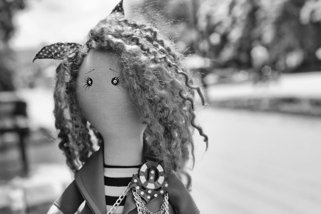 impish: handmade doll with curly red hair in the Park. Black and white photo Stock Photo