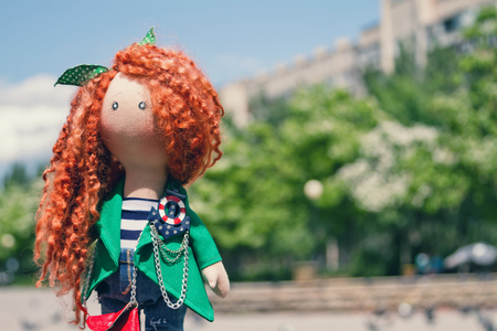 impish: handmade doll with curly red hair in the Park Stock Photo