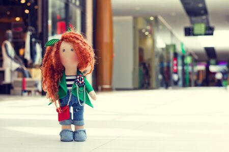 handmade doll with curly red hair walks in the Mall Stock Photo