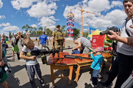 stringent: VOLGOGRAD - SEPTEMBER 10: The boy takes aim with a machine gun at the exhibition of firearms DOSAAF of Russia under the open sky. September 10, 2016 in Volgograd, Russia.