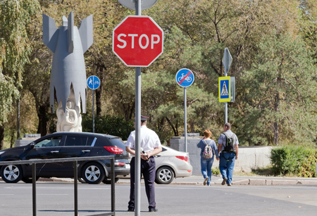 rod sign: VOLGOGRAD - SEPTEMBER 10: A policeman stands at the crossroads with a rod in hands on the background road STOP sign. September 10, 2016 in Volgograd, Russia.
