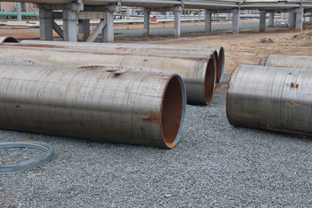 ferrous foundry: Large diameter pipes lying on the gravel on the spot welding of the pipeline