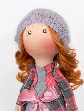 Handmade doll with red hair in a knitted cap Stock Photo