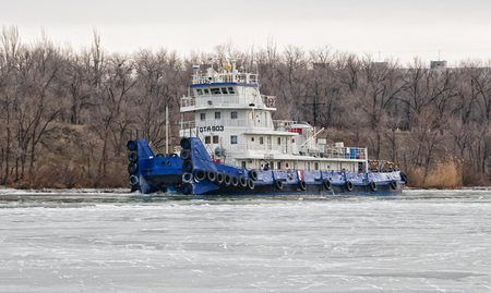 navigable: VOLGOGRAD, RUSSIA - NOVEMBER 27: River tug floats on the navigable channel is already fettered by ice. November 27, 2016 in Volgograd, Russia. Editorial