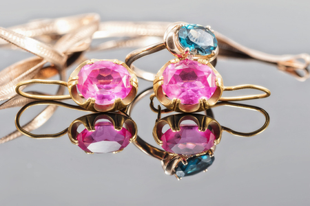 Gold ring with Topaz color London blue and earrings with large rubies on the reflecting surface Stock Photo