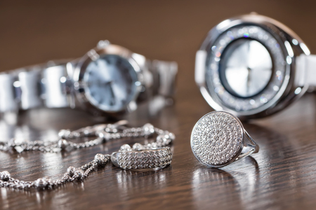 personal ornaments: silver jewelry with cubic Zirconia on a background of elegant womens watches