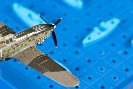 Toy military airplane with propeller is attacking ships on the game Board
