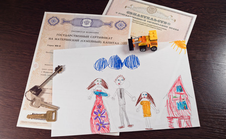 daughter in law: Documents to receive maternity capital certificate and the right of ownership of real estate are on the table together with childrens drawings about the family