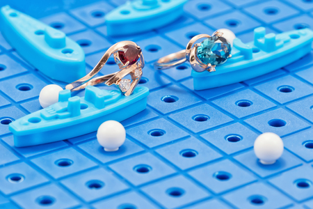 Two gold rings with blue and red precious stones lying on the game Board with toy military ships ready for battle Stock Photo