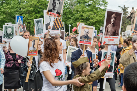 descendants: MOZDOK, RUSSIA - MAY 9: The March of the immortal regiment - descendants are carrying portraits of the war dead relatives. May 9, 2017  in  North Ossetia-Alania, Mozdok, Russia