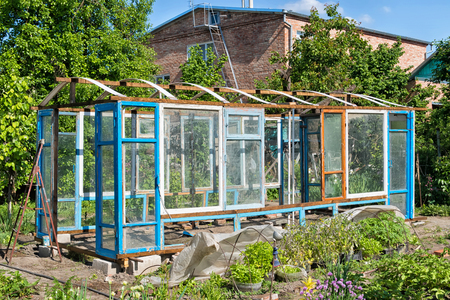 Construction of a greenhouse in the garden from scrap materials and old junk Stock Photo