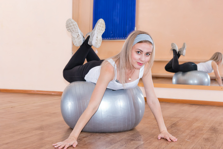 fitball: Graceful young girl lying on a gym ball and looking at the camera