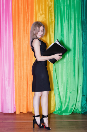 Young seductive woman with a slender figure in a simple black dress and high heels holding a folder of papers