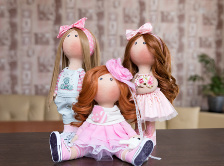Three handmade dolls with natural hair decorated with greenery and small flowers in the interior of the apartment  Stock Photo