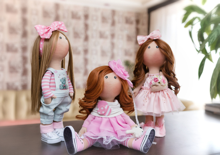 Three handmade dolls with natural hair decorated with greenery and small flowers in the interior of the apartment
