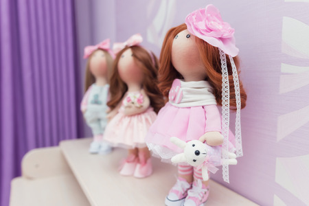 Three handmade dolls with natural hair dressed in dresses and jeans in a room with purple decor