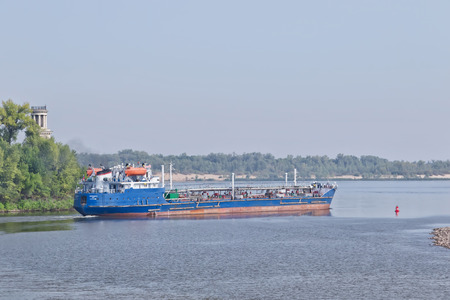 VOLGOGRAD - SEPTEMBER 16: Barge for transportation of various petroleum products turns out of the shipping channel into the channel of the Volga. September 16, 2017 in Volgograd, Russia.
