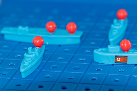 North Korean nuclear submarine with a nuclear missile surrounded by enemies on the Board game battleship Stock Photo