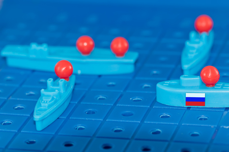 Russian nuclear submarine with a nuclear missile surrounded by enemies on the Board game battleship Stock Photo