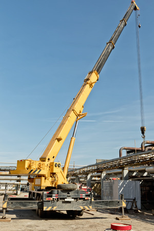 Automotive heavy lift crane is unfolded on the installation of a chemical factory in the time of repair