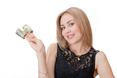 Beautiful young blonde holding between the fingers twisted dollar bills. Isolated portrait Standard-Bild