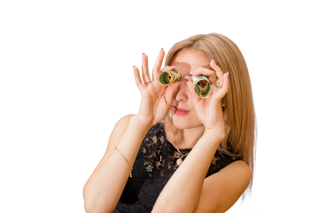 Beautiful young blonde uses twisted dollar bills like binoculars. Isolated portrait Standard-Bild