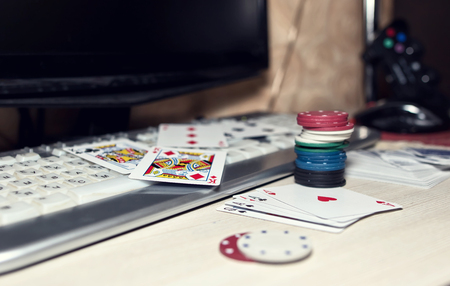 Desk of the player in online casinos with scattered cards and poker chips on the background of the keyboard and gamepad