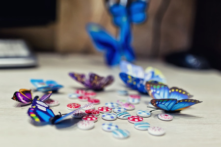 Colorful butterflies and small buttons used for decoration of the apartment on a wooden table Standard-Bild