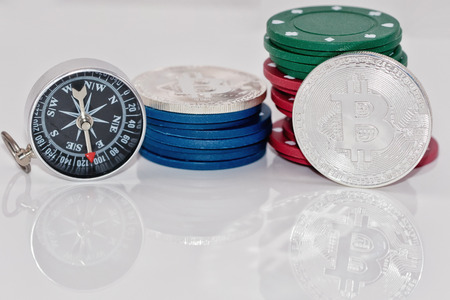 Souvenir coin bitcoin and stack chips from the casinos are next to compass on a reflective surface Standard-Bild