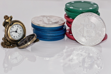 Souvenir coin bitcoin and stack chips from the casinos are next to the pocket watch on a reflective surface