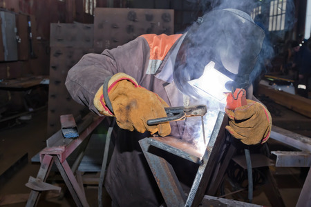 Welder in workshop conditions sample weld from sheet metal to undergo certification. Manual arc welding using remote control