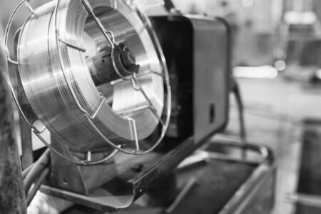 welder for semi-automatic welding with a cylinder of carbon dioxide is in the shop for the production of metal. Black and white photo