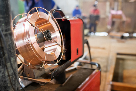 welder for semi-automatic welding with a cylinder of carbon dioxide is in the shop for the production of metal