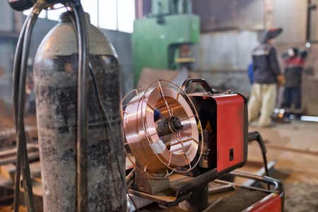 Working atmosphere in an old welding shop with a focus on old hydraulic guillotine and metal profiles