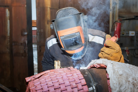 Welder in the shop weld sample from the tube with concomitant heating for attestation. Manual arc welding using remote control Stock Photo