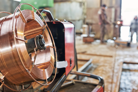 Working atmosphere in an old welding shop with a focus on the coil of welding wire for automatic welding in shielding gases  Standard-Bild