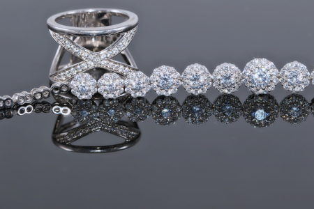 Silver bracelet with many sparkling diamonds and elegant ring with precious stones on a reflective surface