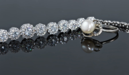 Silver bracelet with many sparkling diamonds and a ring with a jewel on the reflecting surface