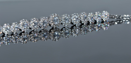 Silver bracelet with many sparkling diamonds on a reflective surface