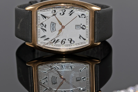 Elegant mens watch in gold with leather strap and broken glass on reflective surface