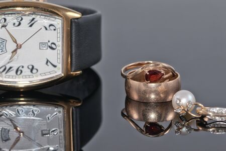 Pair of womens gold earrings with precious stones and engagement ring on reflective surfaces on a background of elegant watches with broken glass