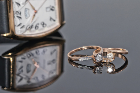 Pair of womens gold rings with diamonds on the reflecting surface on a background of elegant watches with leather strap Standard-Bild