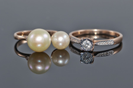 Gold ring with diamond and ring with large pearls on a black reflective surface